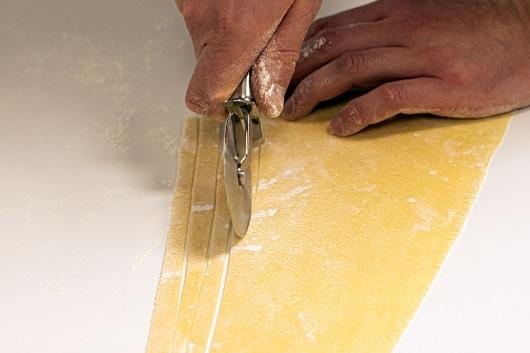 Pastateig mit dem Pizzaroller schneiden