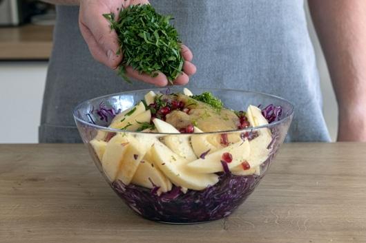 Petersilie an den Salat geben