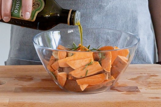 Olivenöl zu den Süßkartoffeln geben