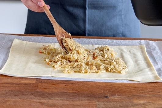 Sauerkraut auf dem Blätterteig verteilen