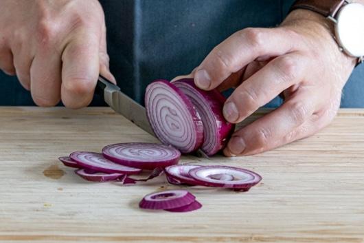 Zwiebeln für die Tomatentarte in Ringe schneiden