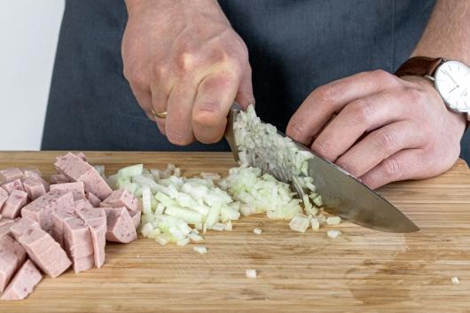 Zwiebel und Jagdwurst würfeln