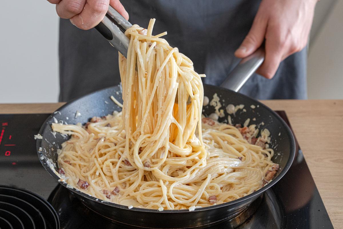 Spaghetti Carbonara mit Sahne durchmischen