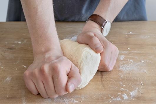 Pizzateig mit den Händen kneten