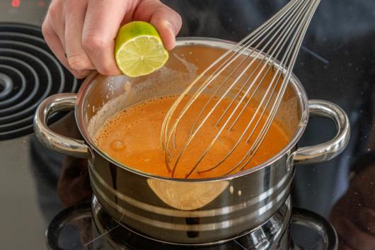 Limette in Erdnussdip pressen