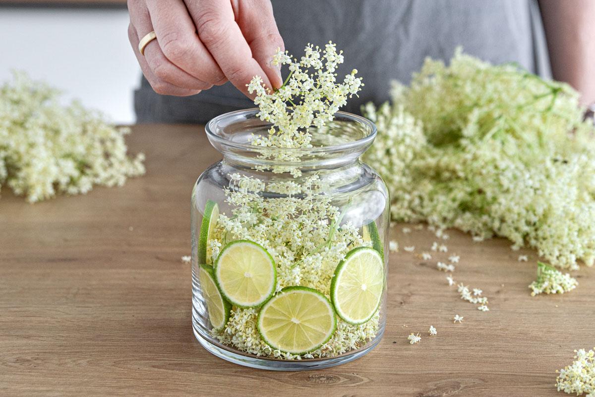 Holunderblüten und Limetten in ein Gefäß geben