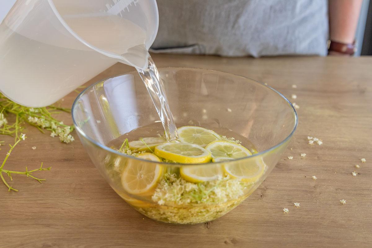 Holunderblüten und Zitrone mit Wasser übergießen