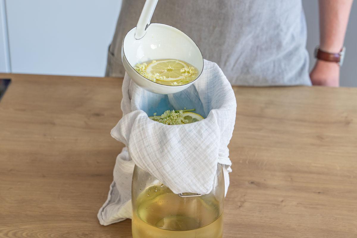Holunder und Zitrone durch ein Tuch geben