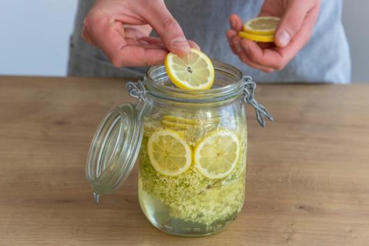Zitronenscheiben zum Holunderblütensirup geben
