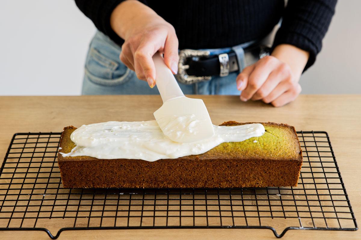 Frosting auf Pistazienkuchen streichen