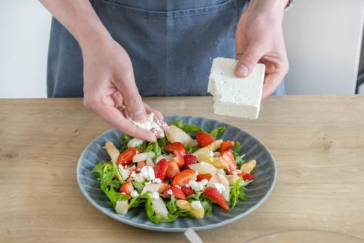 Feta über den Spargelsalat mit Erdbeeren bröseln