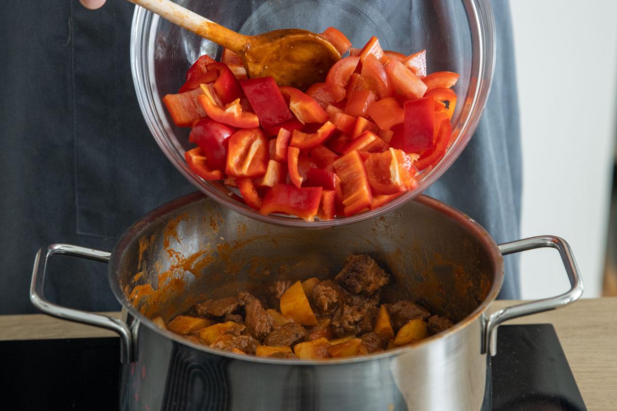 Paprika und Tomaten zum Gulasch geben