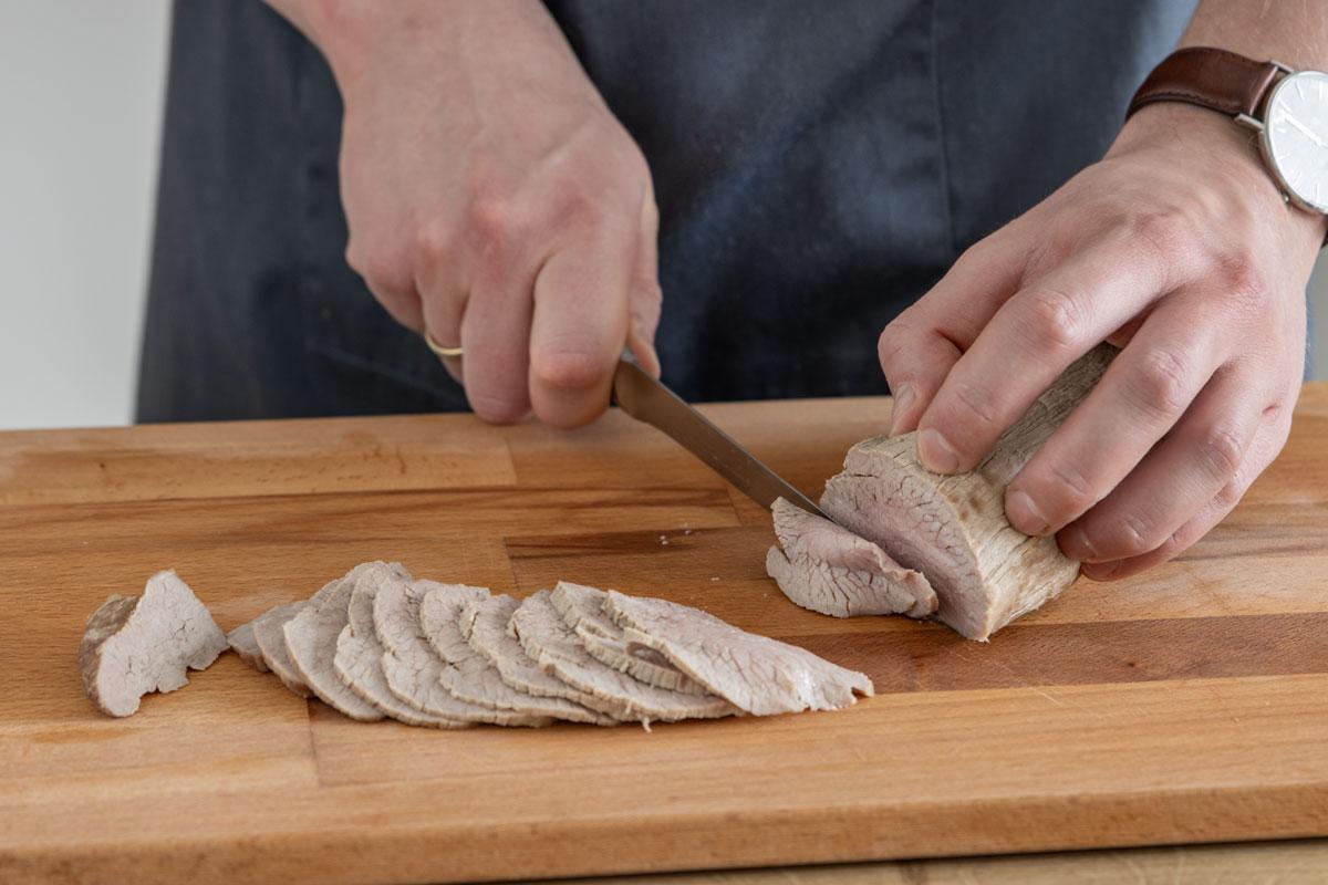 Kalbfleisch in dünne Scheiben schneiden