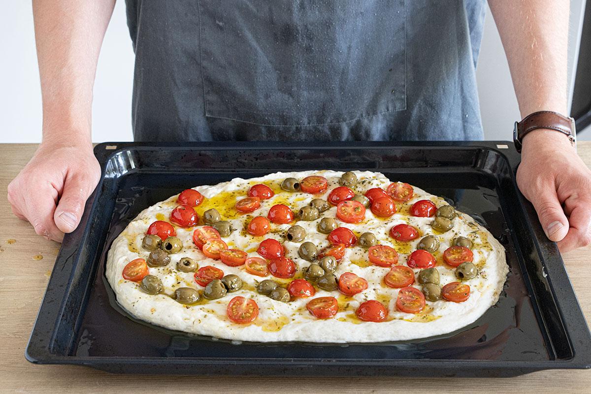 Tomaten-Oliven-Mischung auf dem Teig verteilen