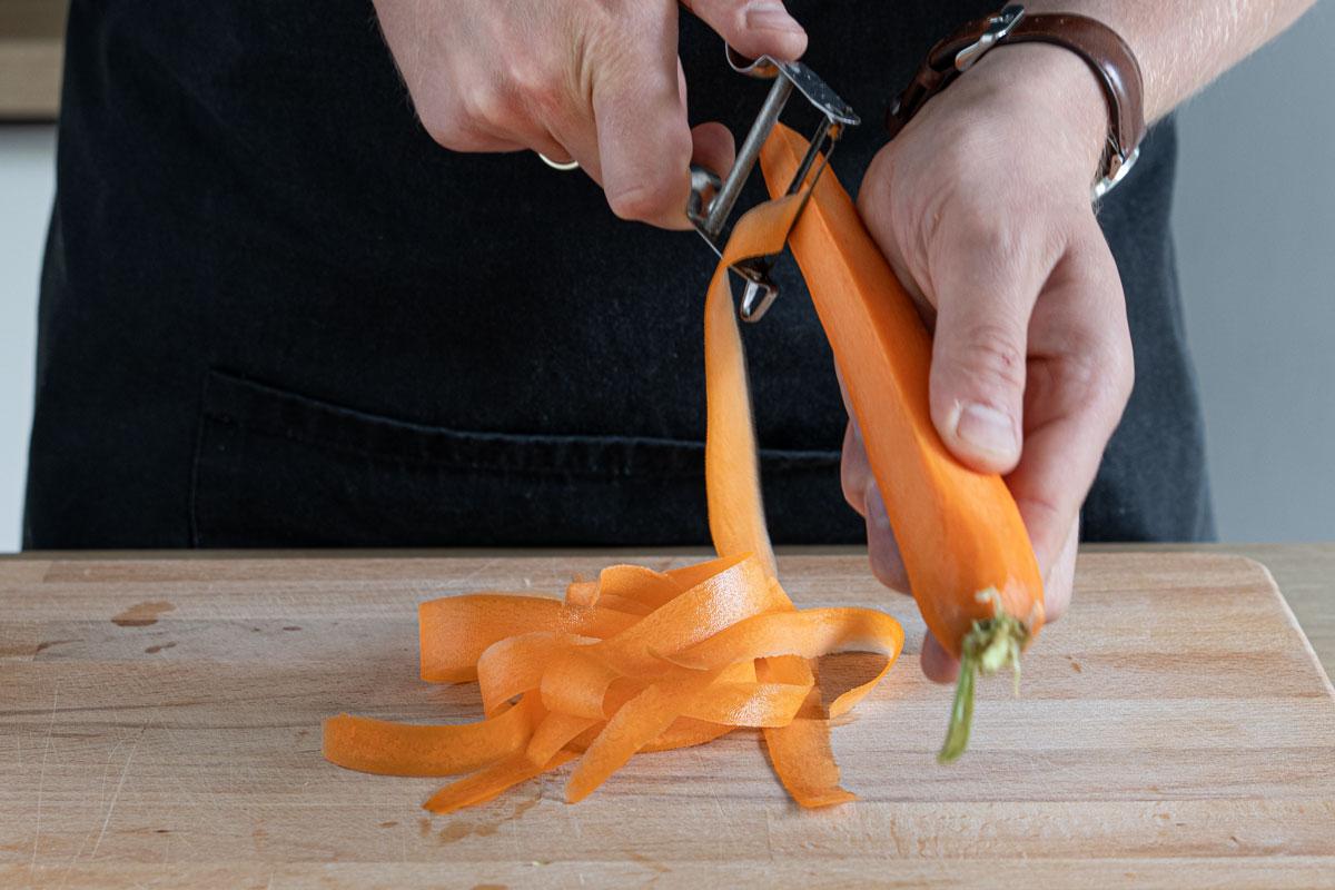 Karotten mit dem Sparschäler in Streifen scchneiden