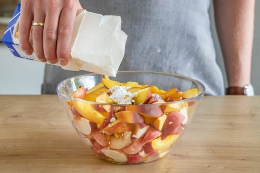 Puderzucker zu Pfirsichen geben
