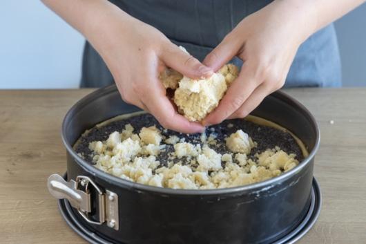 Streusel auf dem Mohnkuchen verteilen