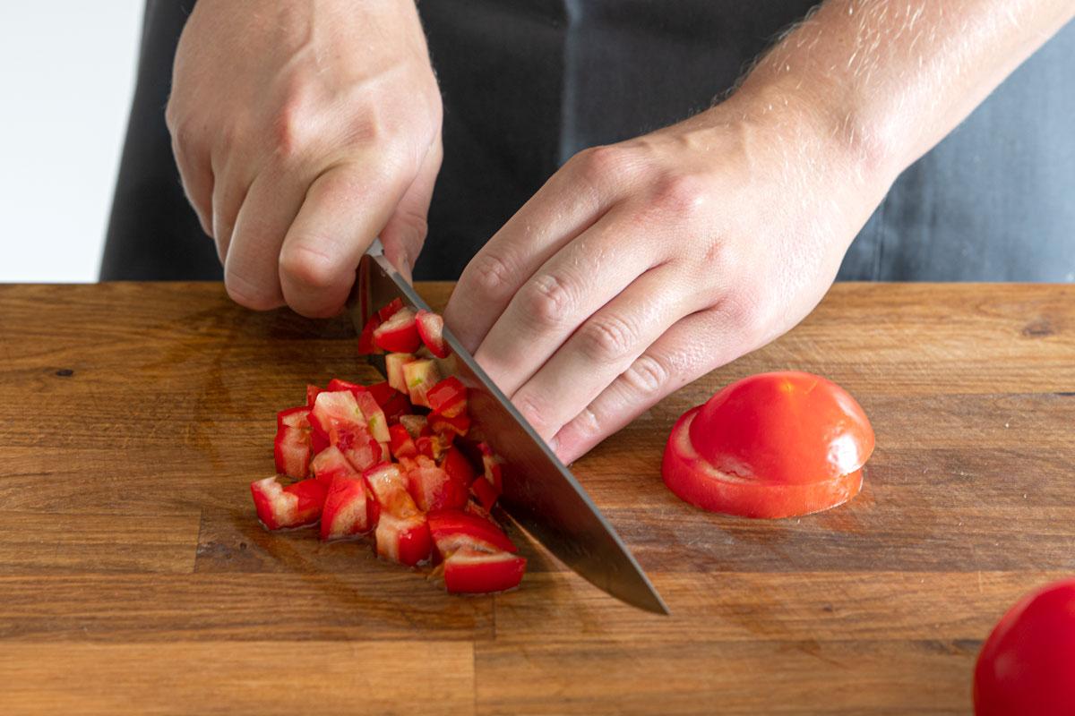 Tomaten in Stücke schneiden