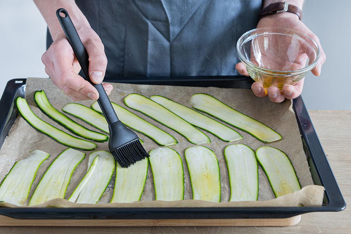 Zucchinistreifen mit Öl einpinseln