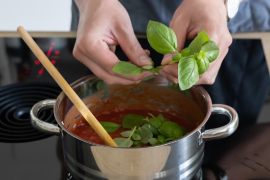 Basilikum zu Tomatensauce für Auberginenauflaufgeben
