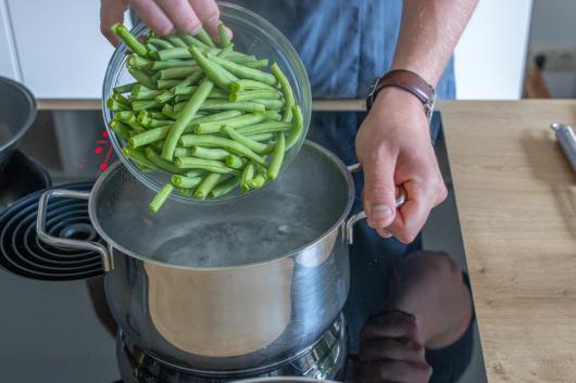 Bohnen in kochendes Wasser geben