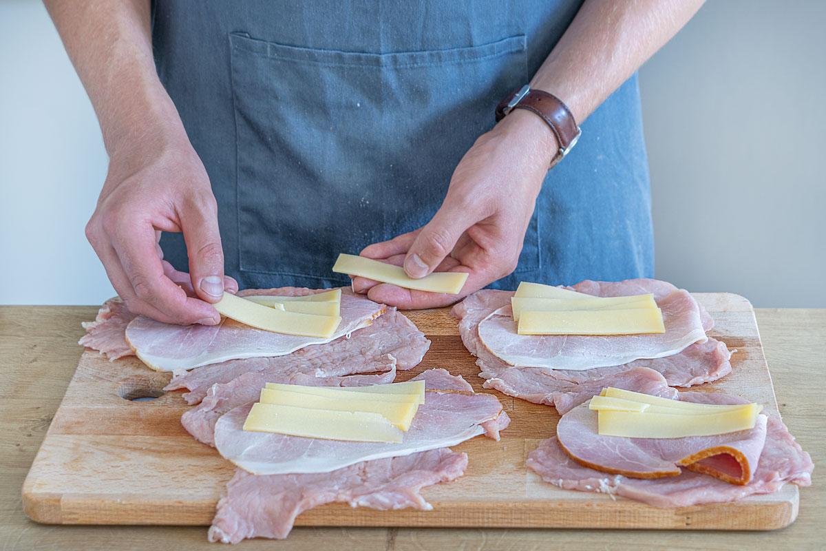 Käse und Schinken auf die Schnitzel geben