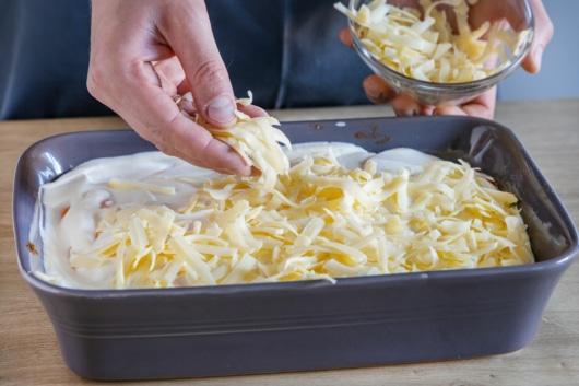 Geriebenen Käse auf Kürbislasagne verteilen