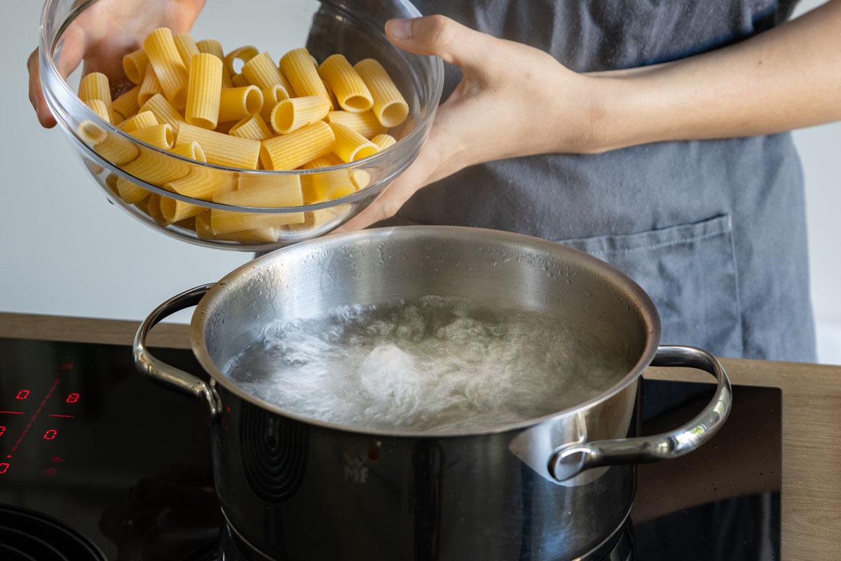 Nudeln in kochendes Wasser geben