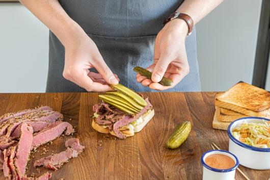 Gewürzgurken auf das Sandwich legen
