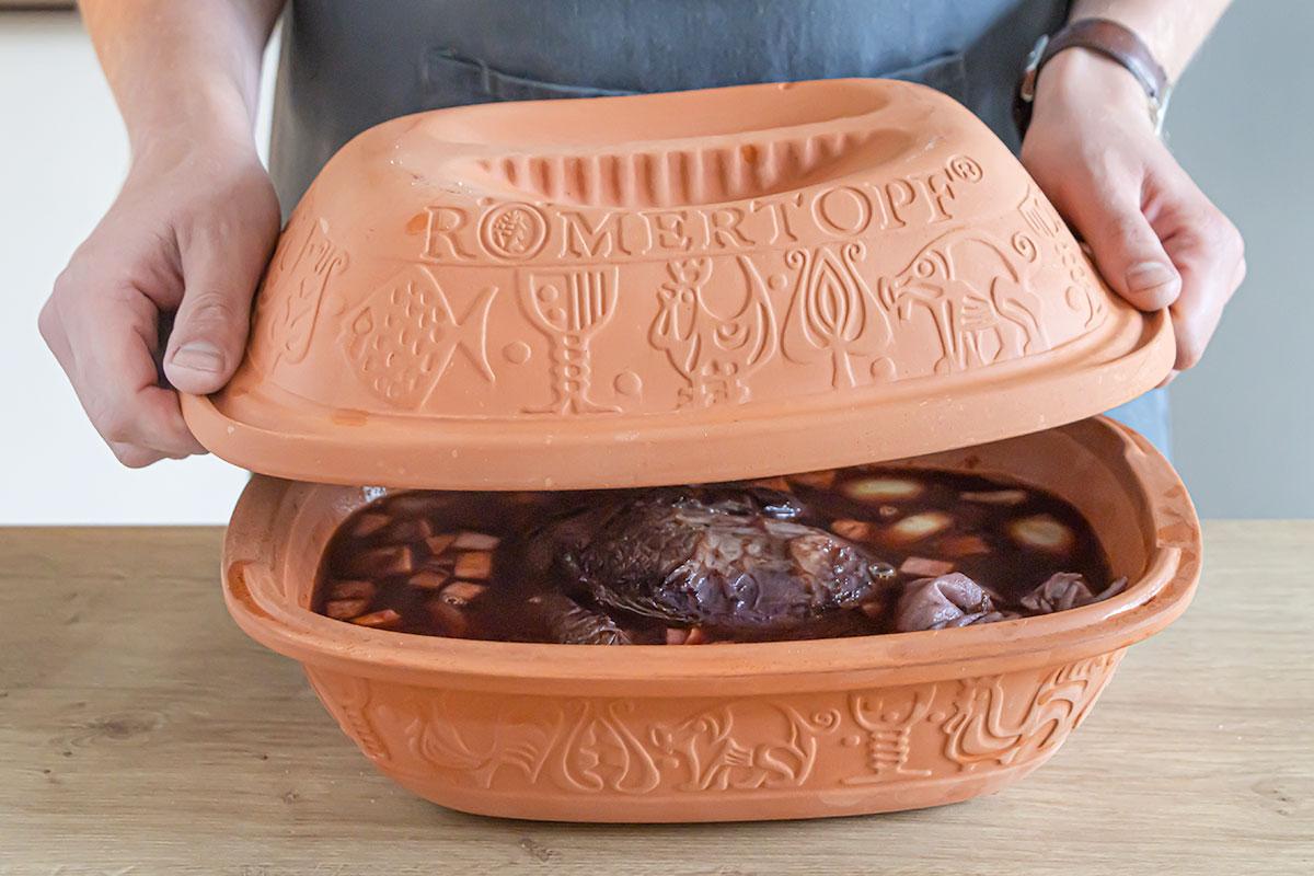 Sauerbraten im Römertopf abdecken und in den Ofen geben