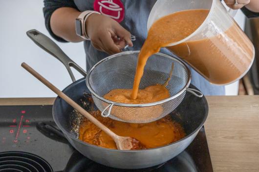 Sahi Paneer Soße in einen Sieb gießen