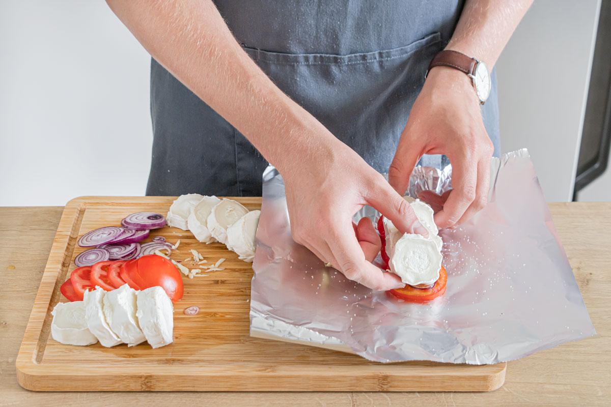 Tomate, Zwiebeln, Knoblauch und Käse auf der Alufolie verteilen