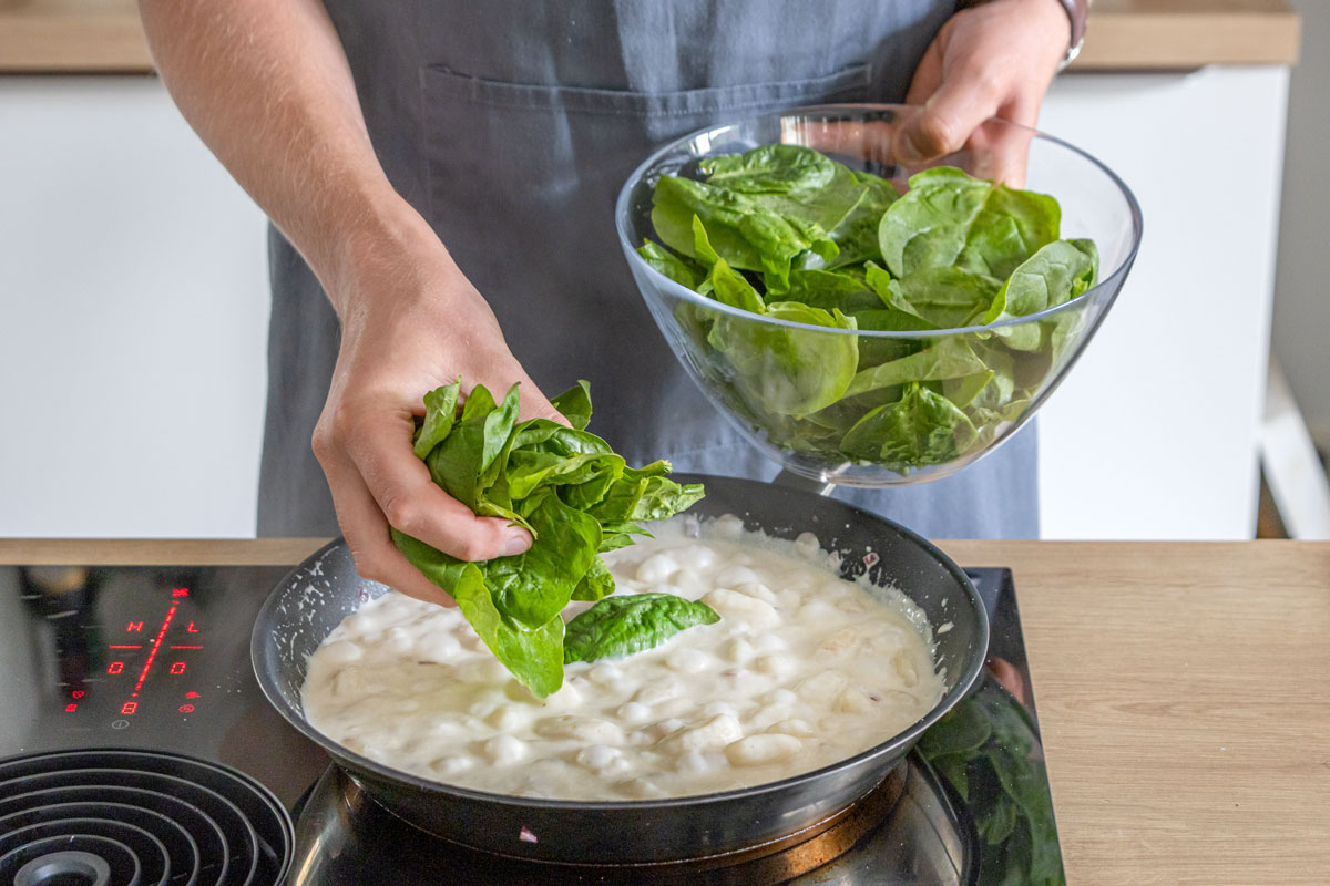 Spinat zu den Gnocchis geben
