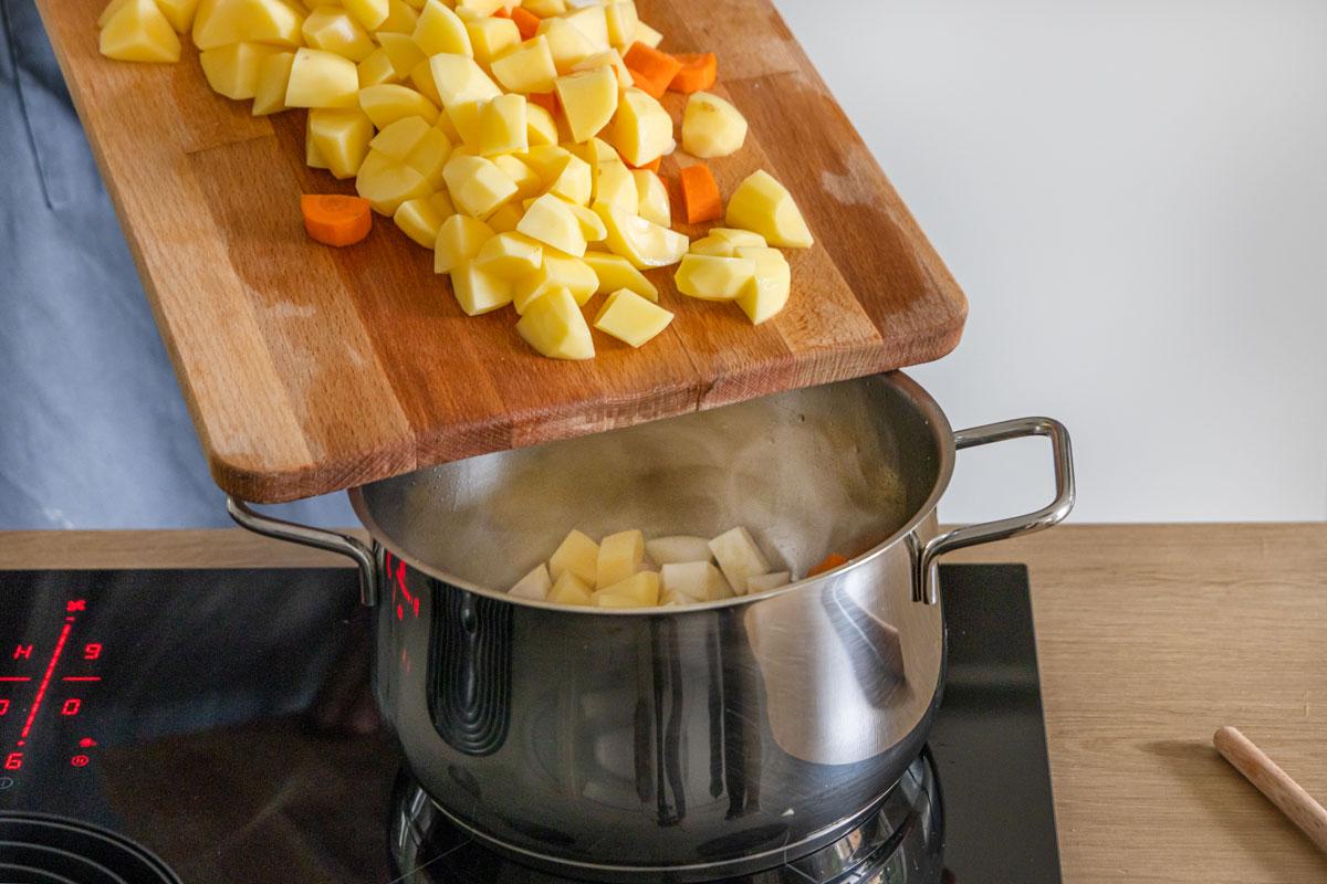 Für Omas Kartoffelsuppe das Gemüse in den Topf geben