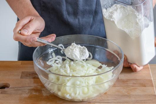Mehl zu den Zwiebeln geben