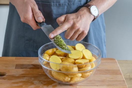 Rosmarin zu den Kartoffeln geben