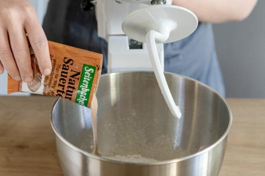 Sauerteig Ansatz zum Mehl geben