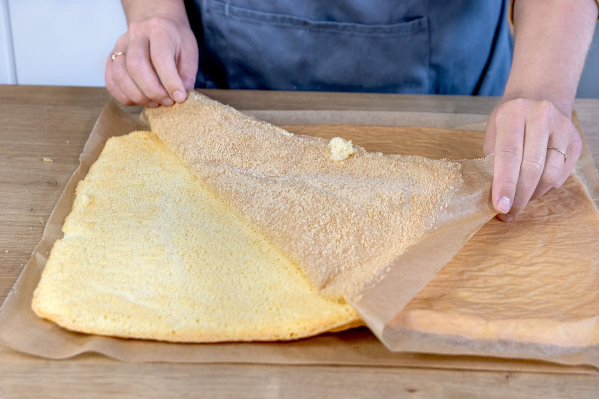 Backpapier vom Teig für die Zitronenrolle abziehen