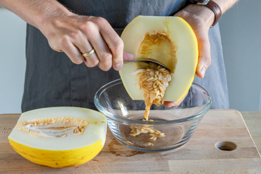Kerne aus der Honigmelone herauskratzen