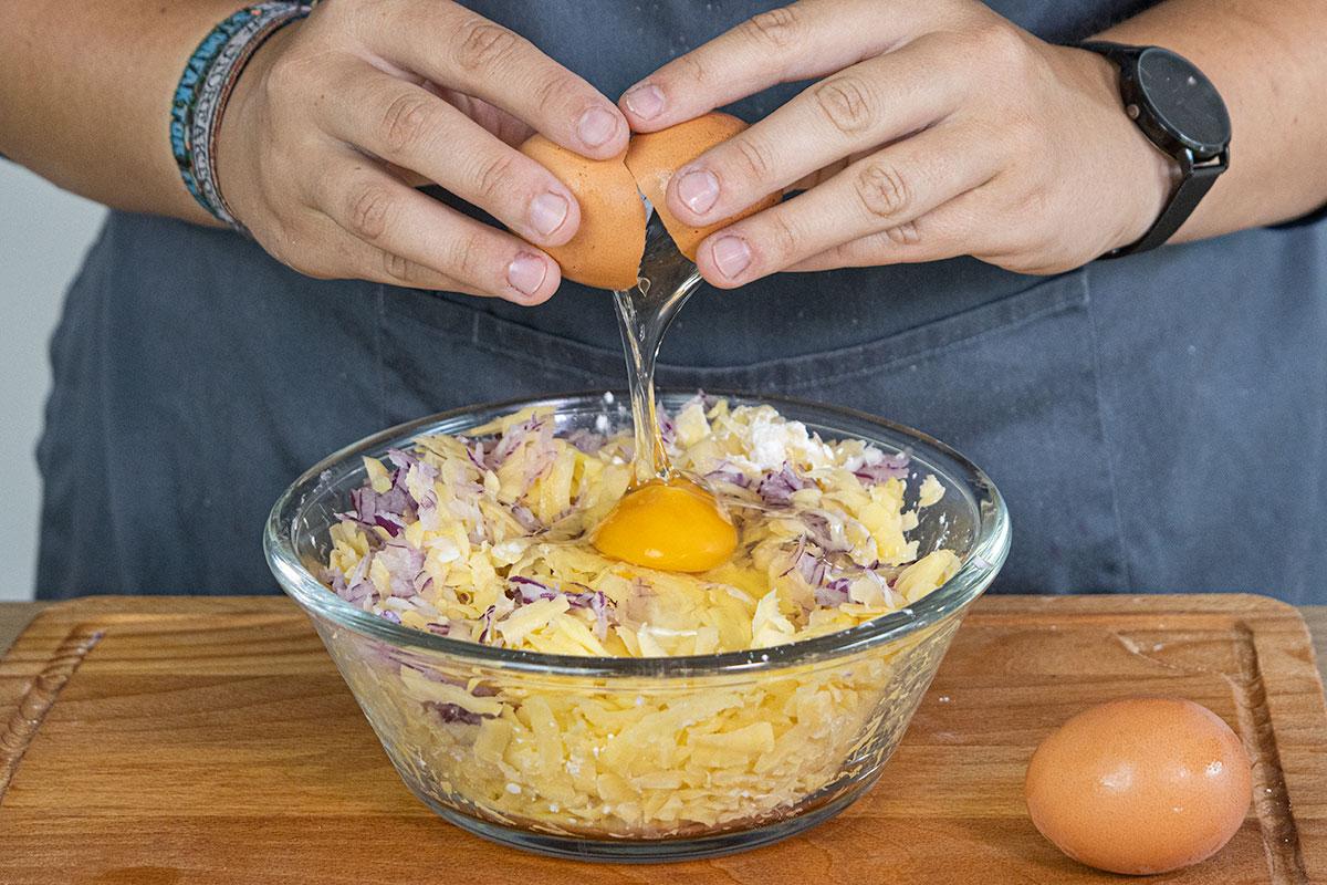 Eier und Gewürze zur Kartoffelmasse geben
