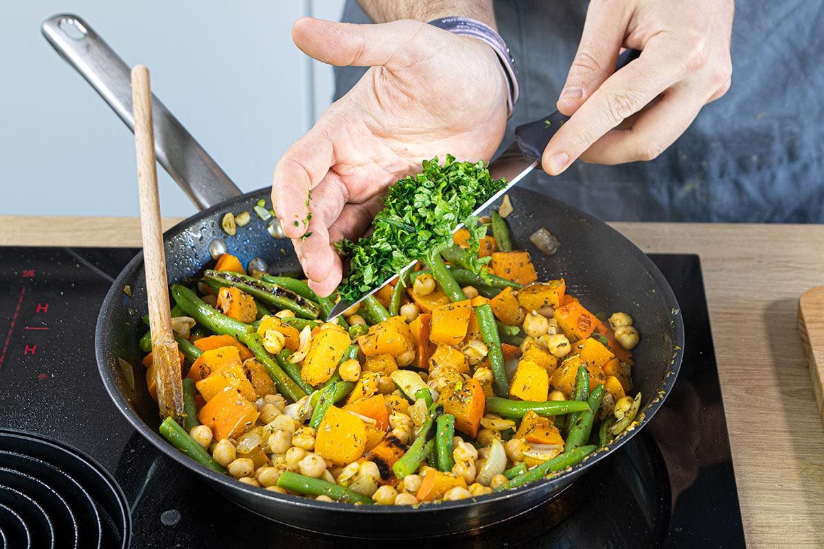 Gemüse Kürbis Pfanne mit Kräutern garnieren