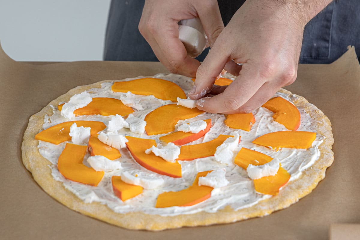 Ziegenkäse auf die Kürbis Pizza zupfen