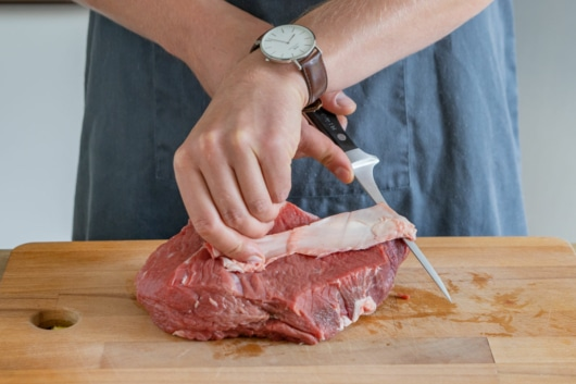 Rinderbraten von Sehnen und Fett befreien
