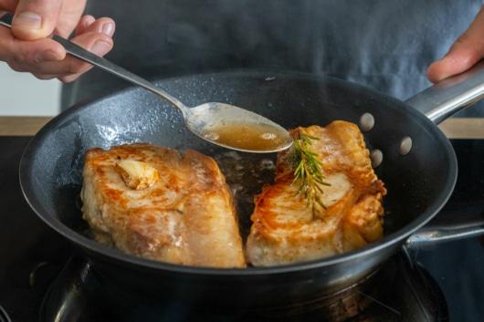 Butterschmalz über Steaks gießen