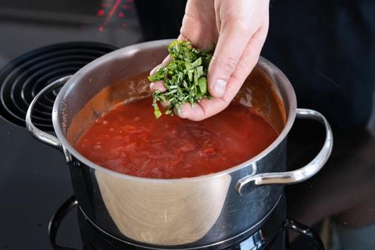 Basilikum zur Tomatensoße geben
