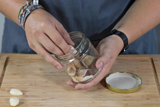 geschälte Knoblauchzehen aus Glas nehmen